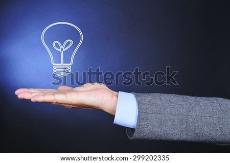 closeup of a man wearing a suit with an illustration of a lightbulb in the palm of his hand - stock photo