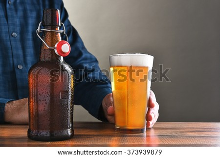 Closeup of a man with a glass of beer and an old fashioned swing top beer bottle. Horizontal format with copy space. - stock photo