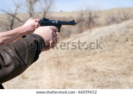 Closeup of  a mans arms pointing a pistol as his instructor shows him.