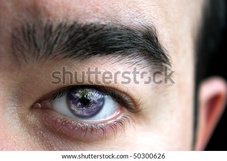 Closeup of a mans eye and eyebrow with the earth superimposed in his iris. - stock photo
