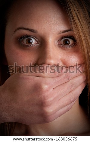 Closeup of a mans hand covering a womans mouth. Concept of domestic violence or kidnapping. Dark mood. - stock photo