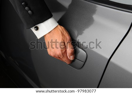 Closeup of a mans hand on the latch of a car door. The valet is wearing a tuxedo.