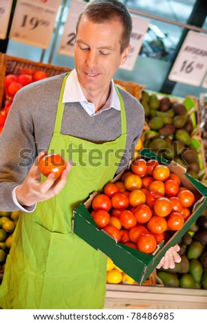 Closeup of a market assistant holding box of tomatoes in the supermarket - stock photo