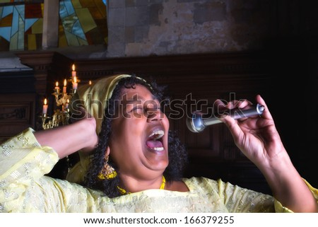 Closeup of a mature gospel or soul singer in a dark church - stock photo
