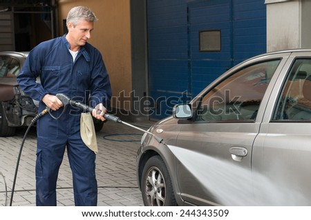 Closeup Of A Mature Man Washing A Car By Pressured Water At Service Station - stock photo