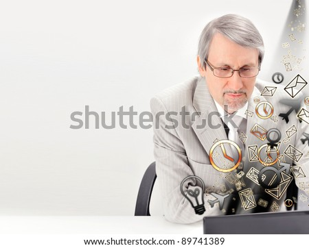 Closeup of a mature smiling business man sitting at his office against white wall and using his modern laptop to do his work