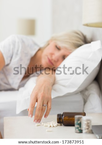 Closeup of a mature woman sleeping in bed with pills in foreground at home - stock photo
