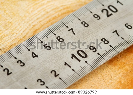 Closeup of a measuring tape on a wooden background - stock photo