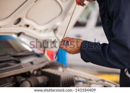 Closeup of a mechanic checking oil levels of a car at an auto shop - stock photo