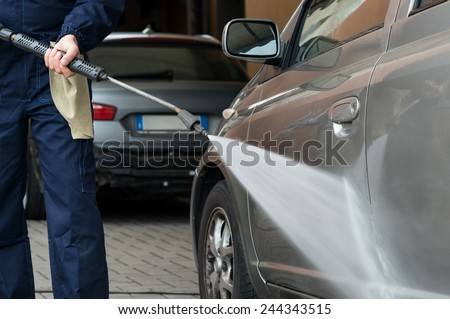 Closeup Of A Mechanic Washing A Car By Pressured Water At Garage - stock photo