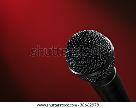 closeup of a microphone against red vignetted  background, may be used for various entertainment or broadcasting themes
