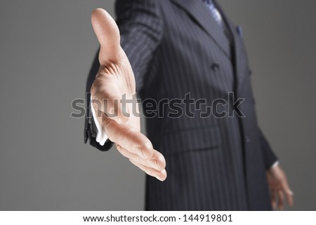 Closeup of a midsection businessman offering hand against gray background