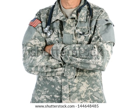 Closeup of a military doctor with a stethoscope around his neck. The man is wearing camouflage fatigues also called ACU and has his arms crossed. - stock photo