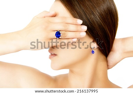 Closeup of a Model Wearing a Tanzanite Designer Ring and Earring, Isolated on White