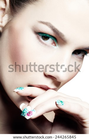 Closeup of a model with cyan eyeshadow and matching nail-art.