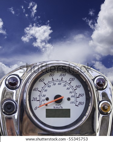 Closeup of a motorcycle speedometer with sky in the background, giving the impression of flying. - stock photo