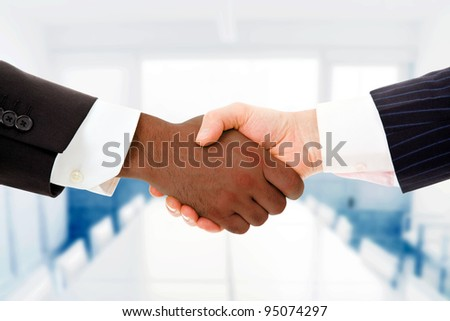 Closeup of a multiracial handshake between two business men at the office - stock photo