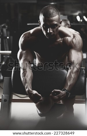 Closeup of a muscular young man lifting weights. Fine art.  - stock photo
