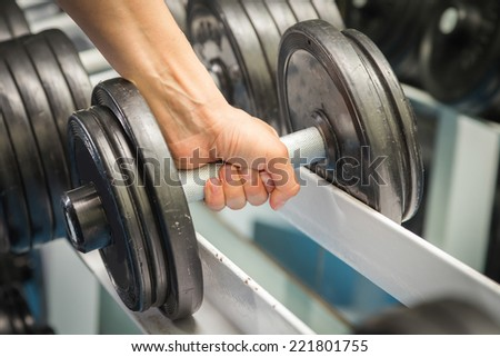Closeup of a muscular young man lifting weights in the gym.Man makes exercises. Sport, power, dumbbells, tension, exercise - the concept of a healthy lifestyle. Article about fitness and sports.