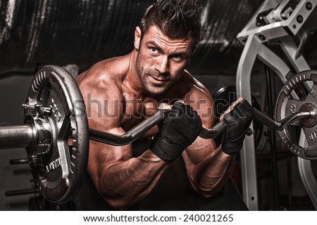 Closeup of a muscular young man lifting weights on dark backgrou - stock photo