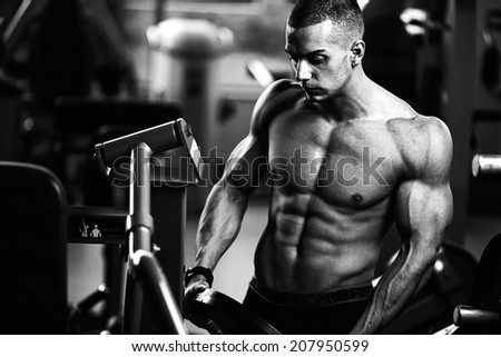 Closeup of a muscular young man lifting weights on dark background  - stock photo