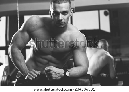 Closeup of a muscular young man lifting weights. Very power athletic guy, in sport-hall.