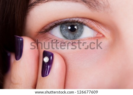 Closeup of a natural beautiful blue-grey female eye with fingertips showing manicured purple nails below - stock photo