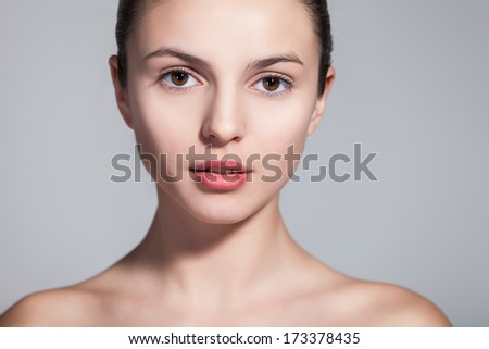 Closeup of a naturally beautiful woman with flawless skin gazing at you on gray - stock photo