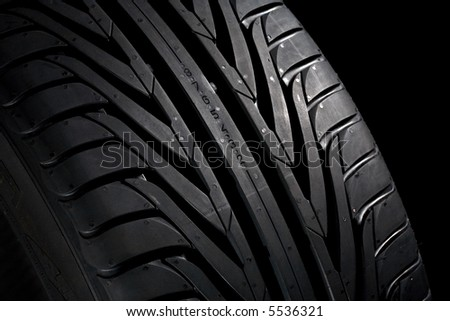 Closeup of a new, black tyre. Black background.