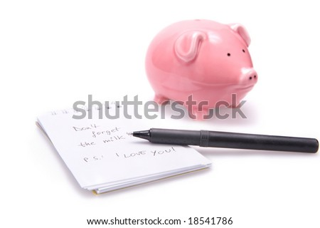 Closeup of a notebook with a shopping reminder on it, a black pen and a pink piggy bank. Isolated on white.