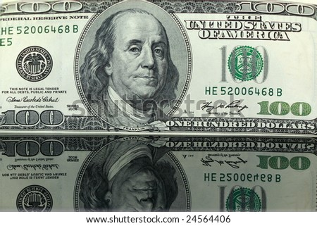 closeup of a one hundred dollar bill reflecting on black