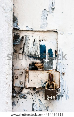 closeup of a padlock on a vintage white door