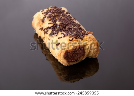 Closeup of a pain au chocolat or napolitana. Isolated on a black background  - stock photo