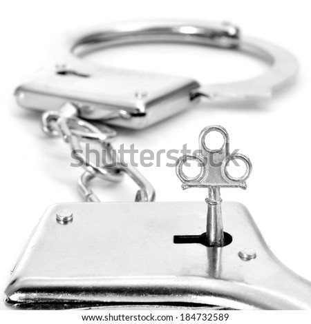 closeup of a pair of handcuffs with a key on a white background - stock photo