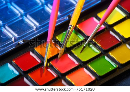 Closeup of a palette of watercolor paints with three brushes - stock photo