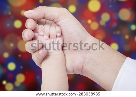 Closeup of a parent hand holds his baby hand, shot with light glitter background - stock photo