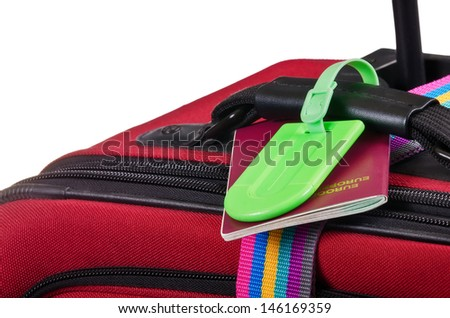 Closeup of a passport and a green luggage tag on red suitcase - stock photo