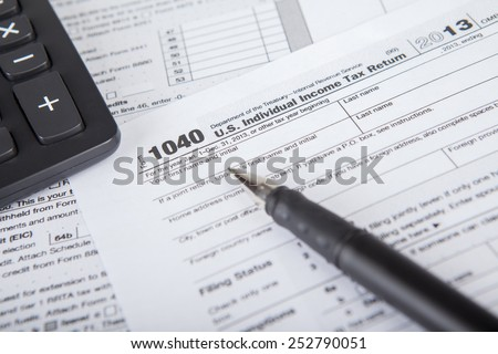 Closeup of a pen pointing at tax form with calculator, symbolizing the time to pay tax - stock photo