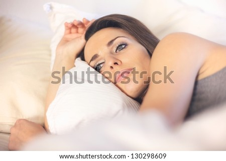 Closeup of a pensive woman lying on bed resting - stock photo