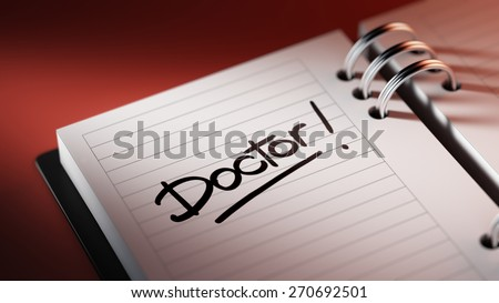 Closeup of a personal agenda setting an important date representing a time schedule. The words Doctor written on a white notebook to remind you an important appointment.