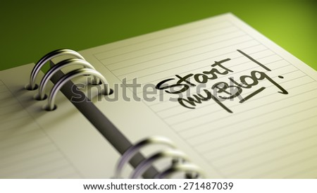 Closeup of a personal agenda setting an important date representing a time schedule. The words Start my Blog written on a white notebook to remind you an important appointment. - stock photo
