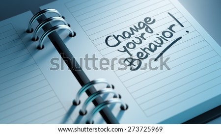 Closeup of a personal agenda setting an important date representing a time schedule. The words Change your behavior written on a white notebook to remind you an important appointment. - stock photo
