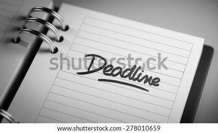 Closeup of a personal agenda setting an important date representing a time schedule. The words Deadline written on a white notebook to remind you an important appointment. - stock photo