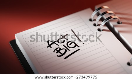 Closeup of a personal agenda setting an important date representing a time schedule. The words Act BIG written on a white notebook to remind you an important appointment.