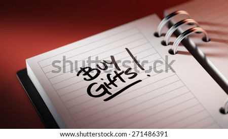 Closeup of a personal agenda setting an important date representing a time schedule. The words Buy Gifts written on a white notebook to remind you an important appointment.