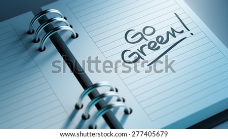 Closeup of a personal agenda setting an important date representing a time schedule. The words Go Green written on a white notebook to remind you an important appointment. - stock photo