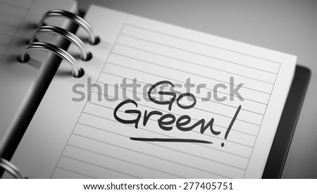 Closeup of a personal agenda setting an important date representing a time schedule. The words Go Green written on a white notebook to remind you an important appointment.