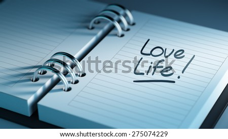 Closeup of a personal agenda setting an important date representing a time schedule. The words Love life written on a white notebook to remind you an important appointment.