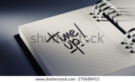 Closeup of a personal agenda setting an important date representing a time schedule. The words Time up written on a white notebook to remind you an important appointment.