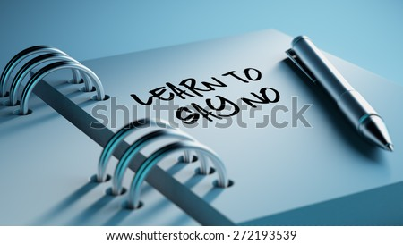 Closeup of a personal agenda setting an important date writing with pen. The words Learn to say no written on a white notebook to remind you an important appointment. - stock photo